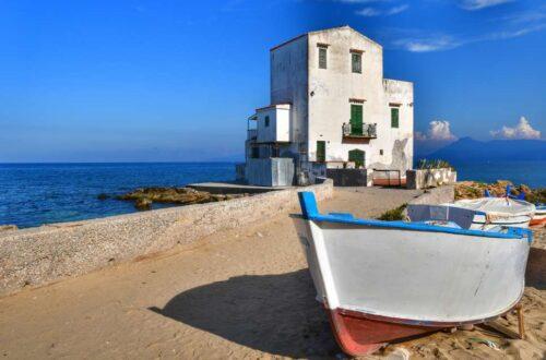 """""""sant elia frazione comune di santa flavia vista spiaggia della casa bianca con barca in primo piano cielo azzurro"""""""