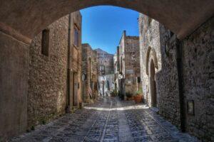 """""""erice una via con case di pietra sotto un arco architettonico"""""""