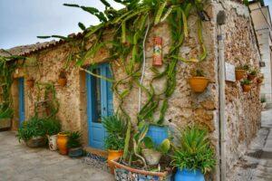 """""""casolare borgo marzamemi in pietra con piante verdi e porta azzurra"""""""