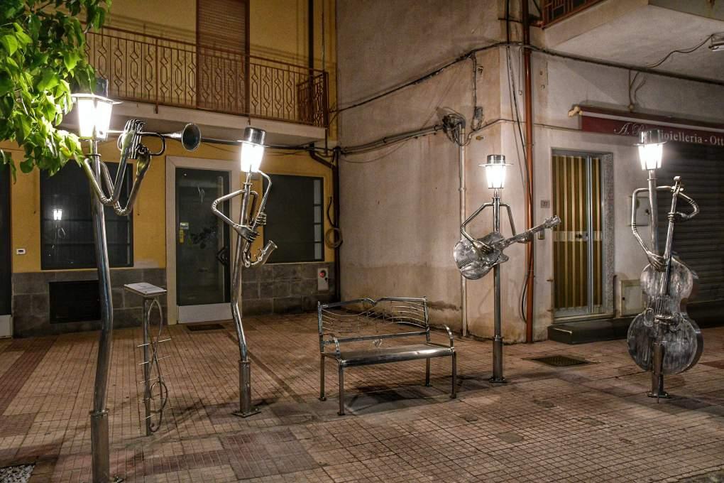 """""""statua musicisti in centro oliveri con lume acceso al posto della testa"""""""