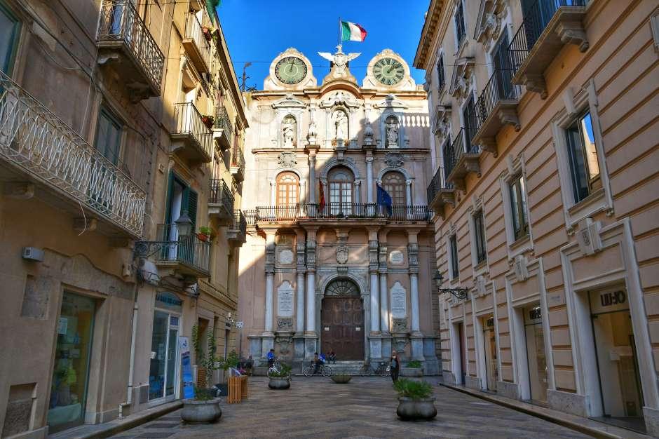"""""""via centro trapani con alla fine palazzo antico con due quadranti d'orologi"""""""