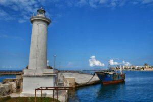 """""""porto di marsala con il faro e vecchio peschereccio ormeggiato nel mare blu"""""""