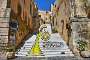 """""""cosa vedere a noto sicilia in questa fotografia una bellissima scalinata dipinta con un fiore gigante"""""""