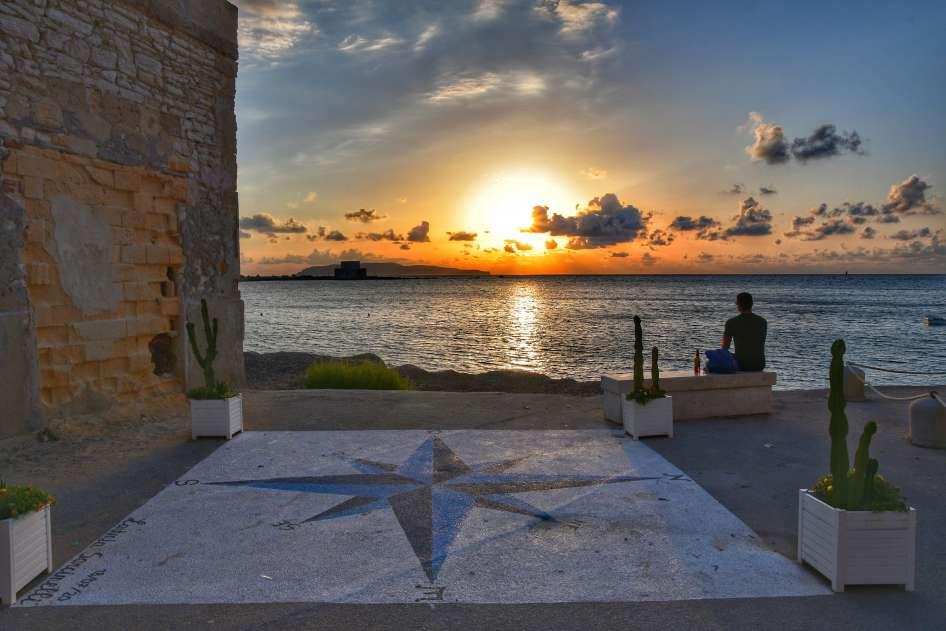 """""""piazzetta del tramonto con rosa dei venti disegnata a terra uomo seduto in panchina e sole tramonta"""""""