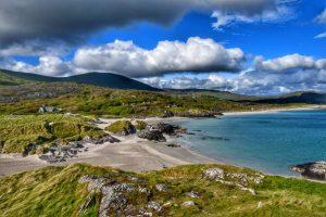 """irlanda spiaggia bianca mare azzurro colline verdi"