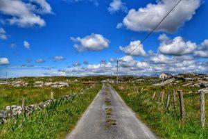 """irlanda strada deserta prati rocce cielo nuvole"""
